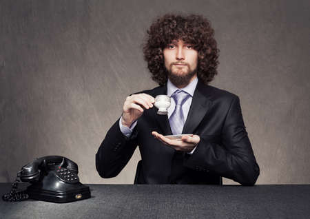 young businessman dinking a cup of coffee or tea on grunge background Stock Photo - 18617262