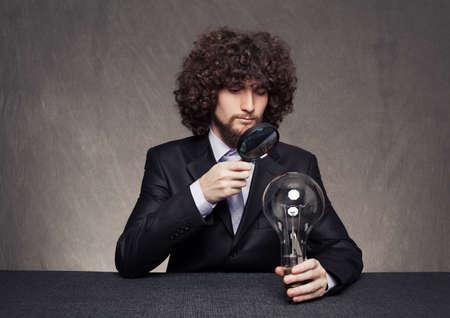 rigorous: uomo d'affari rigoroso esame di una enorme lampadina carefuly con una lente di ingrandimento su sfondo grunge Archivio Fotografico