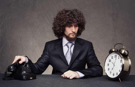 repondre au telephone: jeune homme d'affaires est pr�t � r�pondre au t�l�phone tout en regardant un grand r�veil sur la table sur le fond grunge