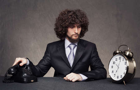 young businessman is ready to answer the phone while looking a big alarm clock on the desk on grunge background photo