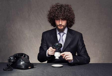 rigorous: rigorosa giovane uomo in tuta esaminando una tazza con una lente di ingrandimento su sfondo grunge