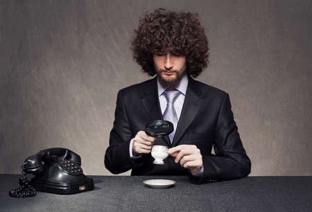 exacting: rigorous young man in suit examining a cup with a magnifying glass on grunge background
