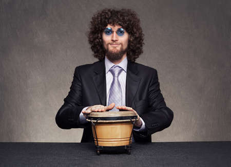 young man with afro style hair wearing a suit and blue eyeglasses playing a hand drum on grunge background Stock Photo