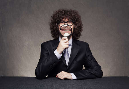 emphasizes: funny businessman emphasizes her smiling mouth with an magnifying glass in his hand on grunge background Stock Photo