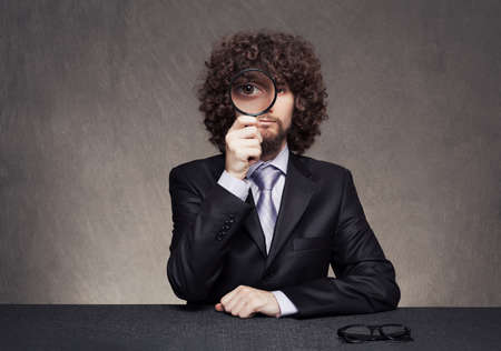 serious afro style haired young businessmas looking through a magnifying glass on grunge background Stock Photo - 18617243