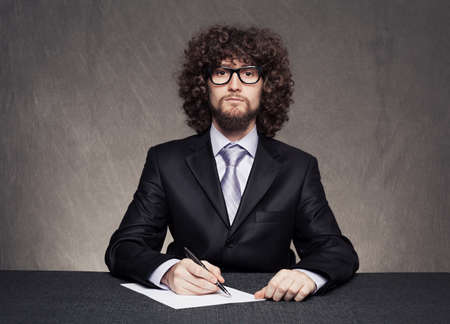 serious businessman with afro style hair and a glasses wearing suit and writing something on blank paper on grunge background Stock Photo - 18617259