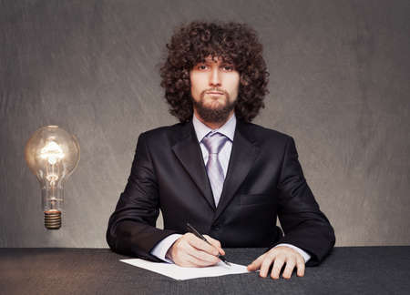 serious businessman is ready to write down the ideas while a glowing bulb standing in th air on grunge background photo