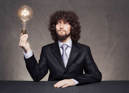 satisfied businessman holding a lightbulb in his hand on grunge background photo