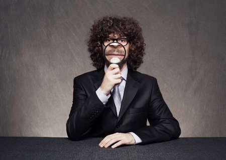 boca cerrada: hombre de negocios serio que sostiene una lupa mostrando su boca cerrada y sin duda no sonr�e en fondo del grunge