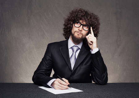 young businessman sitting and thinking with his finger on his head while holding a pen with his other hand on grunge background Stock Photo - 18617338