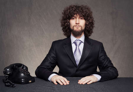 young serious businessman and and a vintage telephone on grunge background Stock Photo - 18617263