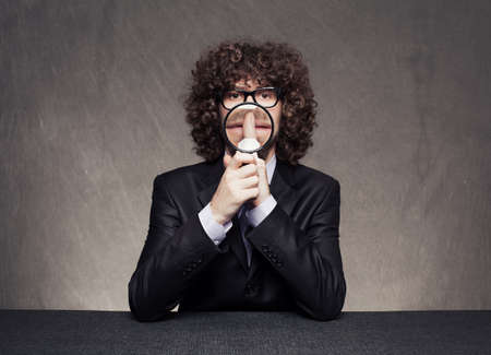 well dressed businessman holding a magnifying glass makes shh with his finger on grunge background Stock Photo - 18617343