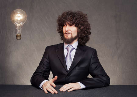 surprised young businessman looking a tungsten lamp on grunge background photo