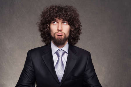 afro hair: confused young businessman trying to make a decision Stock Photo