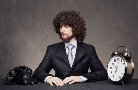 young businessman waiting a phone call with a big alarm clock on desk on grune background