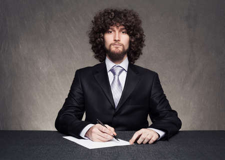 serious businessman with afro style hair sitting on desk and holding a pen on grunge background Stock Photo - 18617261