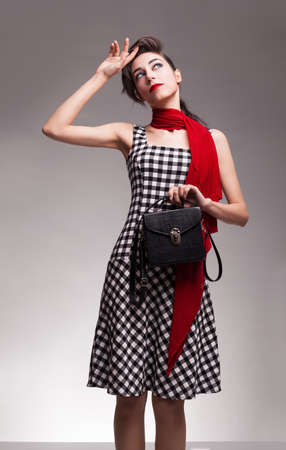 checkered scarf: beautiful brunette fashion model with checked dress fixing her hair with her hand on grey background