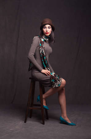 turkish woman: beautiful brunette model sitting on a stool and looking at camera with her blue eyes on grunge background Stock Photo