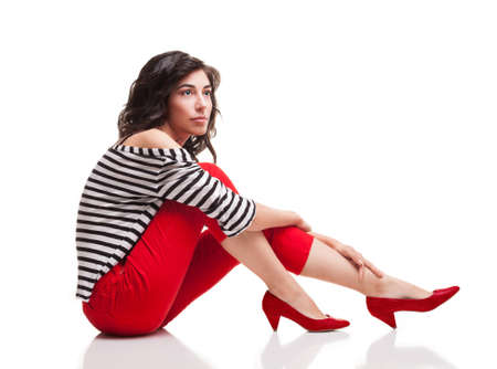 capri pants: young lady wearing casual clothes sitting and looking somewhere isolated on white background