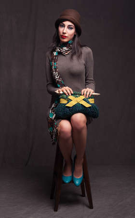 young beautiful lady sitting on a stool and holding a knitted hand bag on grunge background Stock Photo - 18617178