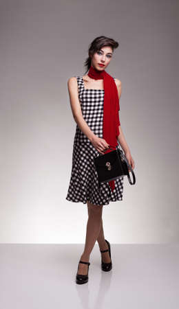 beautiful fashion model with checkered dress carrying a black leather handbag and looking at camera on grey background Stock Photo - 18616945