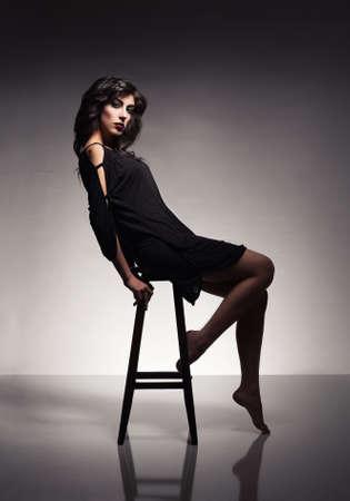 pies sexis: bella modelo brunnete joven sentado y posando en un taburete sobre fondo gris