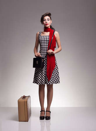 goon: young woman with cute dress,handbag and suitcase is ready to go.on grey background