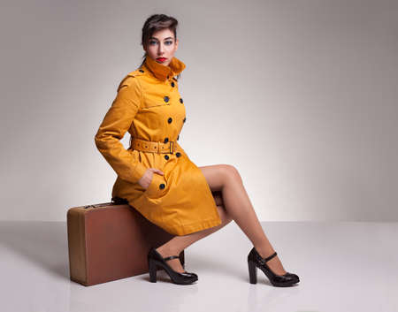 topcoat: beautiful brunette model with her hand in her pocket posing with her yellow overcoat while sitting on her retro suitcase on grey background