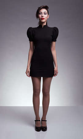 poses de modelos: atractiva morena modelo joven de pie y mirando a la c�mara sobre fondo gris