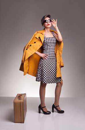 cuadros blanco y negro: hermosa mujer joven con gafas de sol y chaqueta de color amarillo sobre fondo gris posin