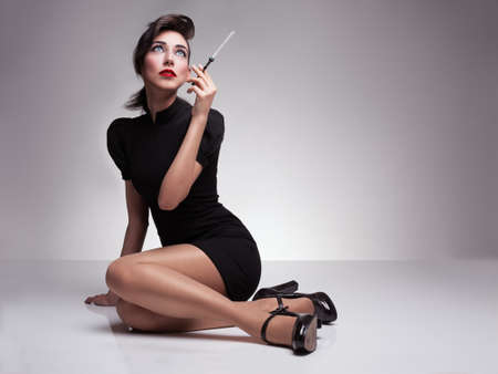 to tight: beautiful lady with black dress and high heels holding a cigarette and looking up on grey background