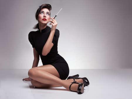 medias veladas: hermosa mujer con vestido negro y zapatos de tacón alto sosteniendo un cigarrillo y mirando hacia arriba sobre fondo gris