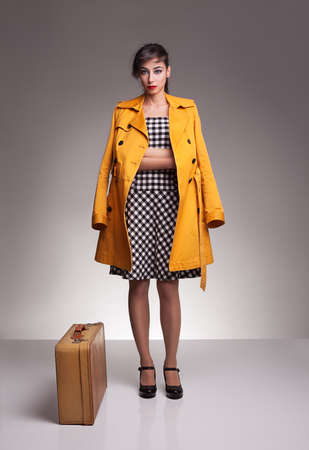 shoe model: young fashion model wearing yellow topcoat standing and posing with her leather retro suitcase