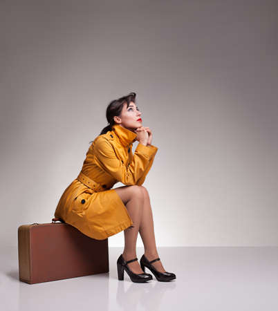 beautiful brunette model sitting on a retro suitcase waiting for something and looking up on grey background photo