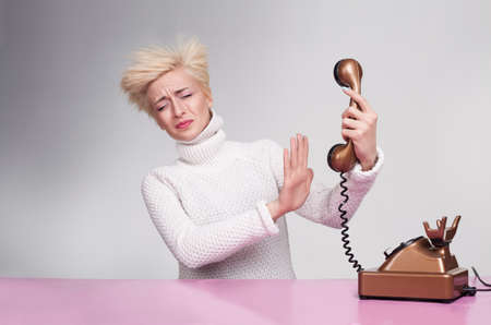 platinum hair: yound lady trying to hold back the handset of an antique phone