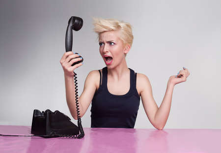 angry young lady shouting and holding handset in her hand Stock Photo