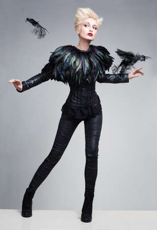 fashion model like bird posing with birds made of smoke on a reflective platform photo
