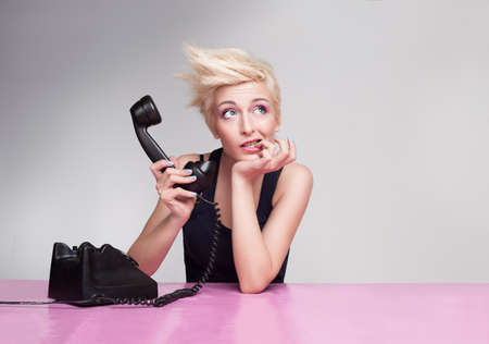 override: young lady thinking with her finger in her mouth and holding handset of antique phone