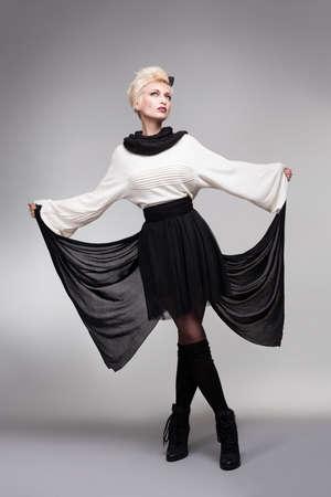 long socks: beautiful model holding her dress like a buıtterfly wing on gray bakcground