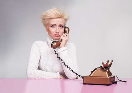 teardrop: young lady wearing white turtleneck sweater getting bad news on the phone and crying Stock Photo