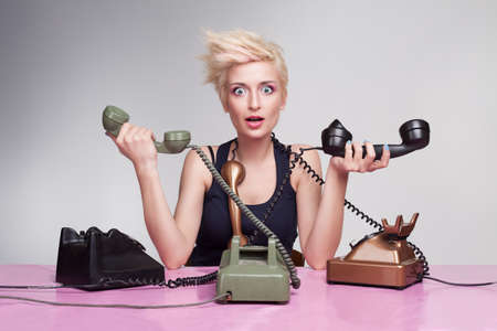 young woman trying to answer the phones but failing Stock Photo