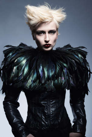 fashion model wearing a costume made of leather and feathers posing on blue background Stock Photo