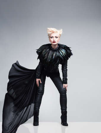 young model wearing leather clothes and feathers posing on  reflective platform photo