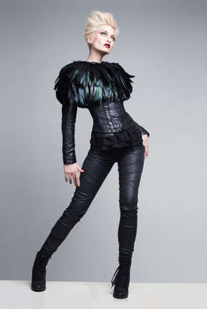 fashion model wearing leather pants and jacket with feathers posing on white platform on grey background