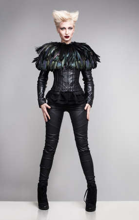 latex girl: futuristic fashion model wearing leather clothes and a blouse made of feathers standing on a white platform and posing Stock Photo