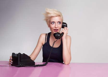 hair short: signora yound con i capelli corti biondi e occhi azzurri spettegolare al telefono Archivio Fotografico