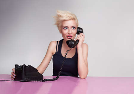 yound lady with blond short hair and blue eyes gossiping on the phone