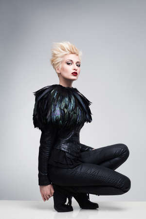 platinum hair: futuristic fashion model on a white reflective platfom posing and looking at camera Stock Photo