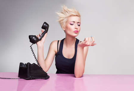 personas escuchando: mujer joven con el pelo corto y rubio que sostiene el auricular y no escuchar el tel�fono