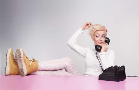 young lady speaking on the phone while her legs on the desk photo